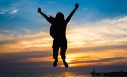 Силуэт девушки скача на море стоковое фото rf