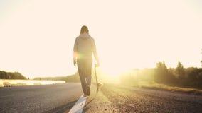 Силуэт девушки с скейтбордом в руках дороги бежать вдоль обочины на заходе солнца задний взгляд медленно сток-видео