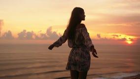 Силуэт девушки с широкими открытыми стойками на скале, заходом солнца оружий на предпосылке ( видеоматериал