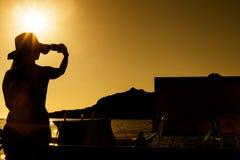 Силуэт девушки фотографируя с мобильным телефоном С sunse Стоковое Фото