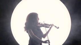 Силуэт девушк-музыканта Скрипач играет скрипку в дыме против белого круга акции видеоматериалы