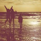 Силуэт детей играя на пляже в зиме Стоковые Изображения