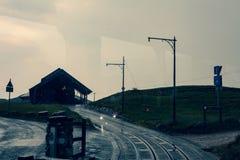 Силуэт дома на холме на сумраке Фантастическое визирование на холме на сумраке Фото от автомобиля на движении Дорога к hou Стоковые Изображения RF