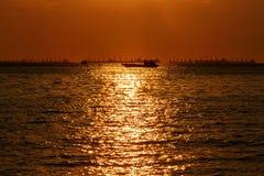Силуэт доставки, рыбацкая лодка с пасмурным красочным небом и солнечный луч starlight на воде отделывают поверхность Стоковая Фотография RF