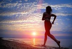 Силуэт женщины бежать на пляже Стоковые Фото