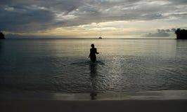 Силуэт женщины гуляя в море Стоковые Фото
