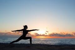 Силуэт женщины делая йогу на пляже на восходе солнца стоковая фотография