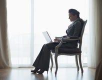 Силуэт женщины дела работая на компьтер-книжке Стоковое Фото