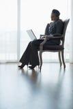 Силуэт женщины дела работая на компьтер-книжке Стоковая Фотография RF