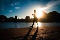 Силуэт женщины идя заходом солнца Стоковое Изображение RF