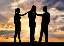 Силуэт женщины и человек нравственно поддерживают другого унылого человека Стоковое Изображение RF