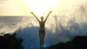 Силуэт женщины на заходе солнца поднимая оружия в воздухе и наблюдая, что океанские волны разбили на утесах и распылять видеоматериал