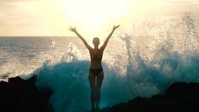 Силуэт женщины на заходе солнца поднимая оружия в воздухе и наблюдая, что огромные океанские волны разбили на утесах и распылять видеоматериал