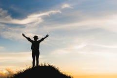 Силуэт женщины празднуя успех na górze холма в стоковое изображение