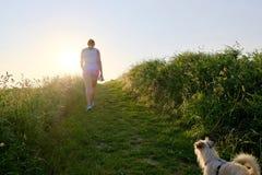 Силуэт женщины при собака идя вверх по пути гравия на заходе солнца Стоковое фото RF