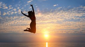 Силуэт женщины скача на пляж, сумерк, космос экземпляра Стоковая Фотография RF
