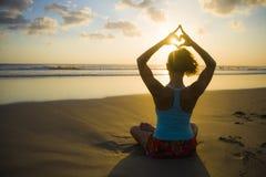 Силуэт женщины спорта детенышей подходящей в практике йоги захода солнца пляжа в раздумье делая форму сердца с руками и пальцами  Стоковые Изображения