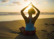 Силуэт женщины спорта детенышей подходящей в практике йоги захода солнца пляжа в раздумье делая форму сердца с руками и пальцами  стоковые фото