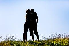 Силуэт женщины целуя человека Стоковые Фото