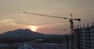 Силуэт здания под конструкцией с краном во время захода солнца, винтажным фильтром видеоматериал
