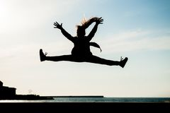 Силуэт здоровой маленькой девочки скача высоко в воздух в городе с морем в лете outdoors Стоковая Фотография RF