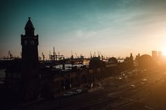 Силуэт известного гамбургера Landungsbruecken с коммерчески гаванью и Эльбой в свете захода солнца последнего вечера, St стоковые изображения