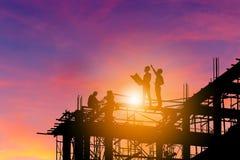 Силуэт инженера и работника на строительной площадке, конструкции стоковые фотографии rf