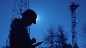 Силуэт инженера на заходе солнца, который смотрит штендеры радиосвязи Инженер пишет данные в планшет _ акции видеоматериалы