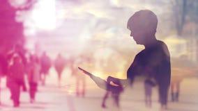 Силуэт интернета просматривать женщины на планшете цифров, отснятом видеоматериале двойной экспозиции