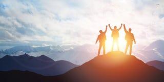 Силуэт команды на пике горы стоковое изображение