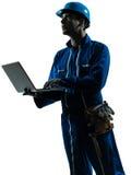 Силуэт компьютера рабочий-строителя человека Стоковое фото RF