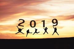 Силуэт 2019 концепции Newyear молодые скакать и руки друга стоковая фотография