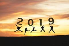 Силуэт 2019 концепции Newyear молодые скакать и руки друга стоковые фото