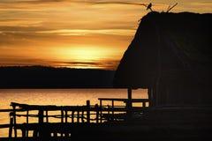 Силуэт коттеджа и птицы на заходе солнца стоковая фотография rf