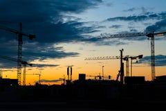 Силуэт кранов башни конструкции на строительной площадке с Стоковое фото RF