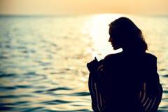 Силуэт красивой женщины стоя с ей назад к камере в морской воде на восходе солнца держа большую широк-наполненную до краев шляпу Стоковые Фото