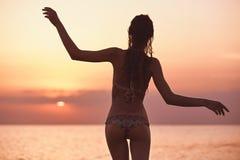 Силуэт красивой сексуальной девушки против моря и захода солнца Стоковые Фотографии RF