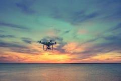 Силуэт летания вертолета квада трутня в небе Стоковое Фото