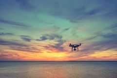 Силуэт летания вертолета квада трутня в небе Стоковое Изображение RF