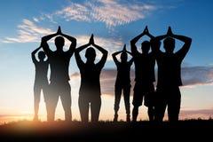 Силуэт людей делая йогу стоковые изображения