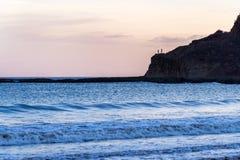 Силуэт 2 людей стоя на утесе на пляже в расстоянии Концепция безмятежности Сан-Хуан del Sur Стоковая Фотография