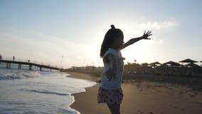 Силуэт маленькой девочки красоты счастливый радостный на излишек пляже захода солнца наслаждаясь природой outdoors, поднимающ рук акции видеоматериалы