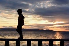 Силуэт мальчика, он идет на парапет На предпосылке моря, заход солнца, красивое небо стоковые изображения