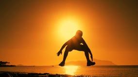 Силуэт мальчика скача на восход солнца