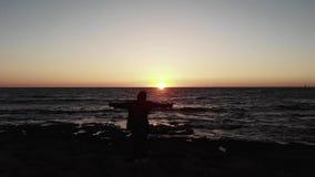 Силуэт молодого женского положения женщины на скалистом пляже с руками широко распространенными к сторонам на заходе солнца над в акции видеоматериалы