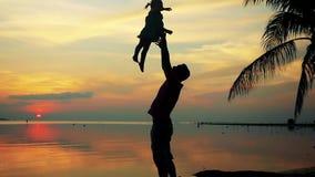 Силуэт молодого отца задерживая его милую дочь младенца в воздухе против красивого неба захода солнца на пальме медленно видеоматериал