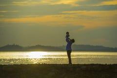 Силуэт молодого счастливого человека с его маленькими сыном или дочерью в его оружиях, отцом поднимая вверх младенца перед морем  стоковое изображение