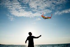 Силуэт молодого человека держа летание змея в голубом небе с облаками на заходе солнца Стоковое фото RF