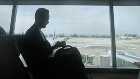 Силуэт молодого человека, который ждет отклонение его полета в авиапорт сток-видео