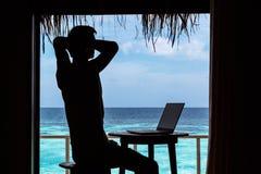 Силуэт молодого человека ослабляя пока работающ с компьютером на таблице Ясная голубая тропическая вода как предпосылка стоковые изображения rf